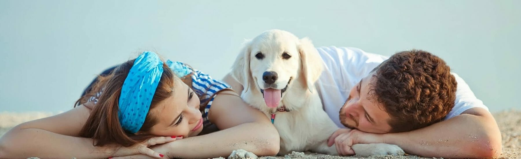 A woman and man lying down on sand with a dog in between them